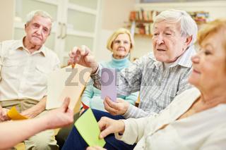 Senioren machen Gedächtnistraining oder Gehirnjogging mit Zetteln im Altersheim