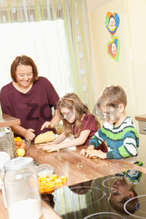 Mother baking cookies with her children