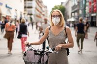Woman walking by her bicycle on pedestrian city street wearing medical face mask in public to prevent spreading of corona virus. New normal during covid epidemic.