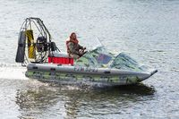 Man in camouflage uniforms and life jacket riding airboat along water surface. Inflatable rubber air boat sail on river at speed
