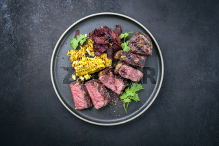 Barbecue dry aged wagyu roast beef steak with corn and vegetable chips offered as close-up on a modern design plate with copy space