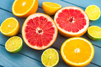 macro photo of bright and juicy orange, grapefruit, lime and lemons that lie on a blue wooden table.