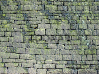 an old grey stone wall made of large irregular blocks covered in patches of moss