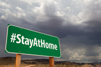 #Stay At Home Green Road Sign Against An Ominous Cloudy Sky