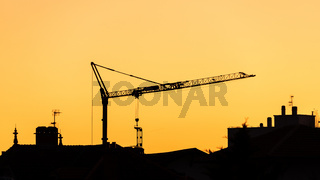 Construction crane silhouette at sunset