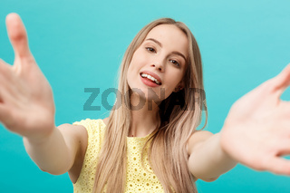 Close-up portrait of attractive young woman stretching her arms, wants to hug you. Isolated on blue background.