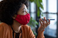 Mixed race businesswoman wearing face mask in creative office