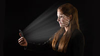 Young Caucasian businesswoman using biometric technology in her phone.