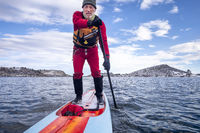 active senior is paddling stand up paddlenboard in winter