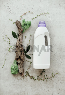 Composition with bottle of laundry detergent by tree bark, tiny mosses and grass on light concrete background