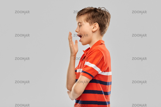 portrait of tired yawning boy in red polo t-shirt