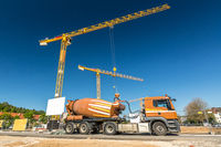 Construction site with concrete mixer truck and cranes