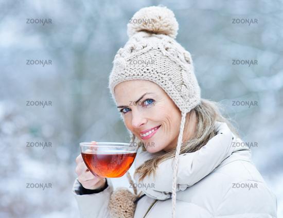 Frau trinkt schwarzen Tee im Winter