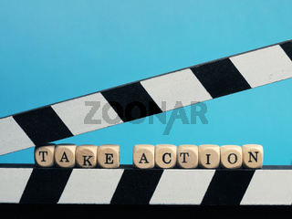 Small wooden blocks with the inscription Take Action on a clapperboard