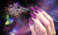 Hand with a beautiful manicure and a brush on a purple bokeh background. Nail design. Extended nails.
