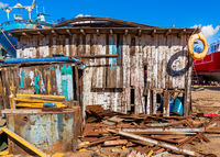 Shabby small building among lot of board with old orange life saver on edge of roof