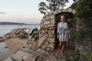 Beautiful woman in luxury summer dress enjoying peaceful seascape of Porto Rafael bay at Mediterranean sea of Costa Smeralda, Sardinia, Italy at dusk