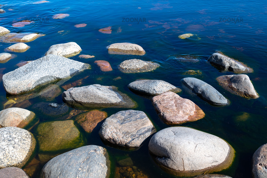 Stones in clear blue lake water. Lake Ladoga, Russia.
