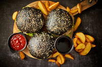 Black burgers and fries with sauce