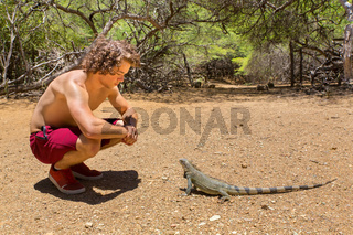 Young man sits with green iguana in nature