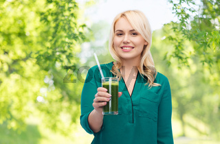 smiling woman drinking vegetable juice or smoothie
