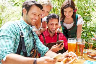 Freunde im Biergarten schauen auf Smartphones