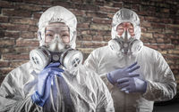 Chinese Woman and Man In Gas Masks, Goggles and Hazmat Suites Against Brick Background