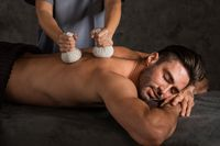 Man getting dry herbs massage