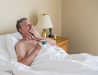 Single caucasian senior man in inclined bed and yawning as if sleepy