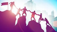 Concept of teamwork with team climbing mountain top