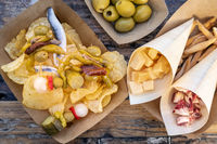 Tapas and pinchos. Cheese, jamon and olives, gildas, fish, potato chips on a wooden table in an outdoors cafe, shot from the top