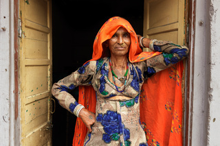 Indian woman with her traditional scarf and dress stands in the entrance of her house.