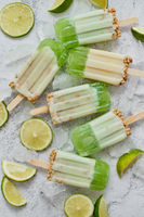 Lime and cream homemade popsicles or ice creams placed with ice cubes on gray stone backdrop
