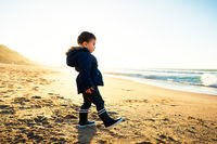 Little boy walking on beach at sunset, winter season