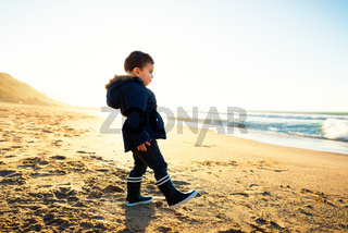 Little boy walking on beach at sunset, winter season