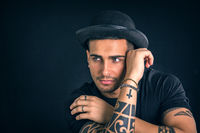 Young man with black bowler hat and tattoos