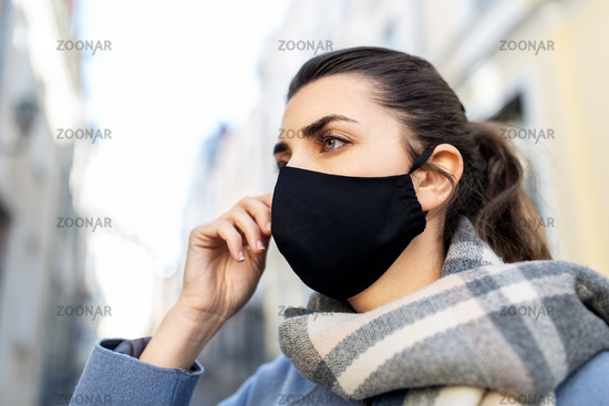 woman wearing protective reusable mask in city