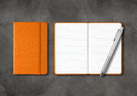 Orange closed and open lined notebooks with a pen on dark concrete background
