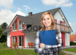Junge Frau steht vor einem Einfamilienhaus