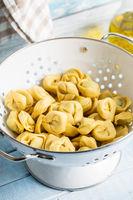 Tortellini pasta. Italian stuffed pasta in colander.