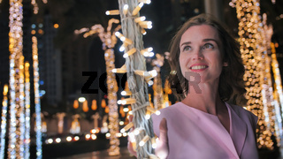 The girl gently touches the glowing lights on a palm tree in the night city of Dubai.