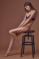Sexy young woman seated on a stool in her lingerie