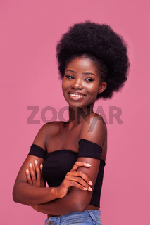 Happy charming African American girl with amazing afro hair standing smiling with arms folded in black top and denim jeans isolated on pink background
