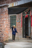 Old Chinese lady walking outside her home