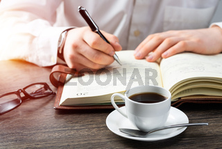 Man making notes with pen in notebook