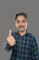 Smiling Indian Trader Man with Moustaches Showing Thumbs Up on Grey Background