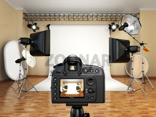 DSLR camera in photo studio with lighting equipment, softbox and flashes.