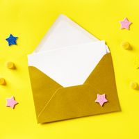 A white greeting card in a golden envelope, overhead square shot on a yellow background with glitter stars