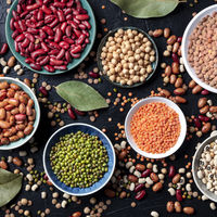 Legumes assortment, overhead square shot on a dark background. Lentils, soybeans, chickpeas, red kidney beans, a vatiety of pulses