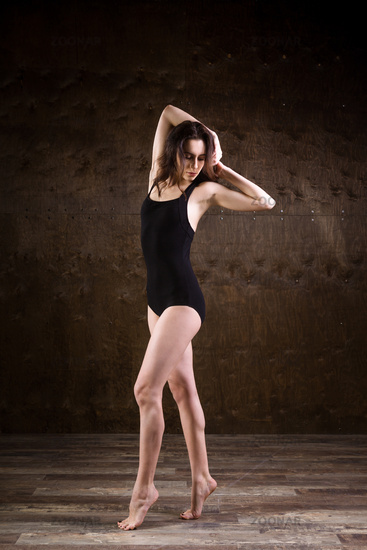 A very thin young girl, full-length with her long, flowing hair, is standing in a black swimsuit on a dark brown wooden background. Weight problems with anorexia nervosa